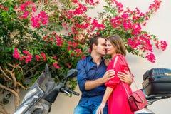 Ung man som omfamnar flickvännen med mjukhetsammanträde på sparkcykeln som parkeras under blommande bougainvilleaträd på den mede royaltyfri fotografi