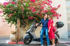 Ung man som omfamnar flickvännen med mjukhetsammanträde på sparkcykeln som parkeras under blommande bougainvilleaträd på den mede fotografering för bildbyråer