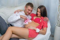 Ung man som omfamnar gravida kvinnan på soffan Fotografering för Bildbyråer