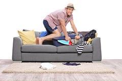 Ung man som packar mycket kläder in i en resväska Arkivfoto