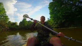 Ung man som paddlar kanoten på floden Handlingkamera som är slowmotion arkivfilmer