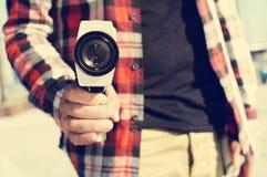 Ung man som pekar en toppen kamera 8 på observatören Royaltyfria Bilder