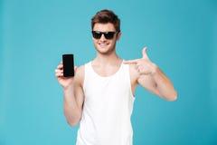 Ung man som pekar på den tomma skärmen av smartphonen som isoleras över blått royaltyfri foto