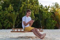 Ung man som placeras på en gunga och att använda hans telefon Vit sand och djungel som bakgrund royaltyfri bild