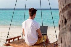 Ung man som placeras på en gunga och att arbeta med hans bärbar dator Klart bl?tt tropiskt vatten som bakgrund royaltyfri foto