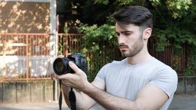 Ung man som poserar med fotokameran Arkivfoton