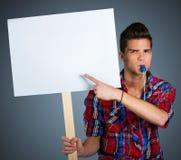 Ung man som protesterar med protesttecknet Arkivbild