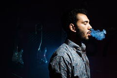 Ung man som röker cigaretten på mörk bakgrund - rök ringer Arkivfoto