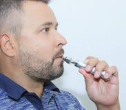 Ung man som röker elektronisk sigarette Arkivfoton