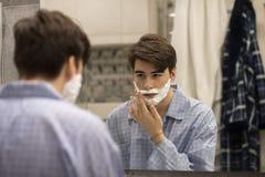 Ung man som rakar för första Gång royaltyfri fotografi