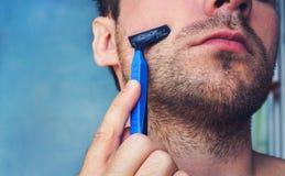 Ung man som rakar hans skägg med en rakkniv Royaltyfri Fotografi