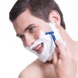 Ung man som rakar skägget med rakkniven Royaltyfri Fotografi