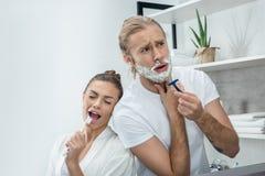 Ung man som rakar skägget med rakkniven medan lycklig kvinna som sjunger i tandborste Royaltyfria Bilder