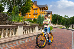 Ung man som rider en färgrik gul cykel Arkivbild