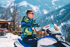 Ung man som rider en snövessla på ett spår i mitt av de österrikiska fjällängarna fotografering för bildbyråer
