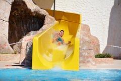 Ung man som rider ner en vattenglidbana-man som tycker om en vattenrörritt Fotografering för Bildbyråer
