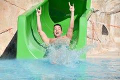 Ung man som rider ner en vattenglidbana-man som tycker om en vattenrörritt Arkivfoto