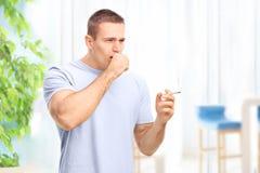 Ung man som röker en cigarett och hosta Royaltyfri Bild