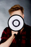 Ung man som ropar i megafon Royaltyfri Fotografi