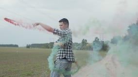 Ung man som rotera kulör rök poi på den lantliga vägen