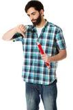 Ung man som rymmer den stora röda blyertspennan royaltyfria foton