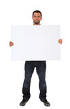 Ung man som rymmer det blanka vita tecknet Royaltyfri Foto