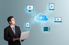 Ung man som rymmer en bärbar dator och framlägger beräknande networ för moln Royaltyfri Bild
