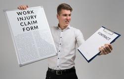 Ung man som rymmer en form med en reklamation av skadan på arbete och den tomma avtalsformen som isoleras på en ljus bakgrund arkivbilder