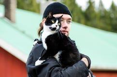 Ung man som rymmer en katt Fotografering för Bildbyråer