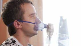 Ung man som rymmer en maskering från en inhalator hemmastadd Behandlar inflammation av flygbolagen via nebulizeren Förhindra astm lager videofilmer