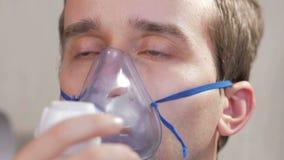 Ung man som rymmer en maskering från en inhalator hemmastadd Behandlar inflammation av flygbolagen via nebulizeren Förhindra astm stock video