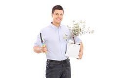 Ung man som rymmer en olivträdväxt och en spade Royaltyfri Fotografi