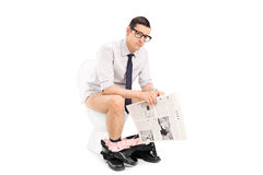 Ung man som rymmer en tidning placerad på toalett Royaltyfri Fotografi