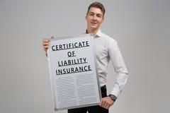 Ung man som rymmer ett certifikat av ansvarsförsäkring isolerat på en ljus bakgrund royaltyfri fotografi
