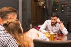 Ung man som rynkar pannan och känner sig borrad med hans romantiska vänner royaltyfria foton