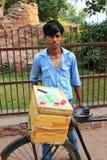 Ung man som in säljer efterrätter från en cykel utanför Jama Masjid Arkivbild