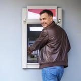 Ung man som sätter in en kreditkort till ATM royaltyfri foto