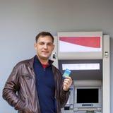 Ung man som sätter in en kreditkort till ATM royaltyfri fotografi