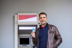 Ung man som sätter in en kreditkort till ATM royaltyfria foton