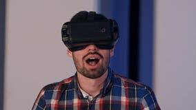Ung man som sätter på vrexponeringsglas och tycker om virtuell verklighetvärlden Arkivbild