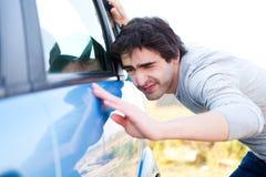 Ung man som söker efter skrapor på hans bil Fotografering för Bildbyråer