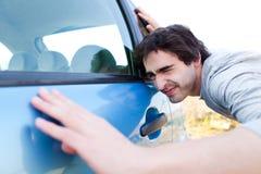 Ung man som söker efter skrapor på hans bil Arkivfoton