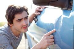 Ung man som söker efter skrapor på hans bil Arkivbilder