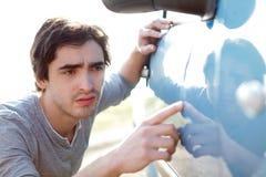 Ung man som söker efter skrapor på hans bil Royaltyfria Bilder