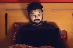Ung man som ser bärbara datorn och får förbluffad i mörker fotografering för bildbyråer