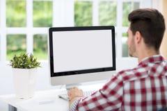 Ung man som ser datorskärmen royaltyfria foton