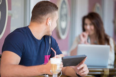 Ung man som ser flickan i ett kafé Fotografering för Bildbyråer