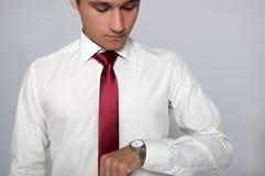 Ung man som ser hans armbandsur Fotografering för Bildbyråer