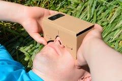 Ung man som ser in i exponeringsglas för en virtuell verklighet arkivfoton