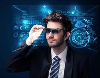 Ung man som ser med futuristiska smarta tekniskt avancerade exponeringsglas Arkivbild
